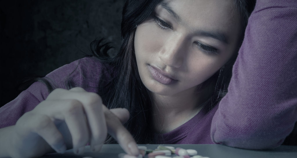 Portrait of teenge girl choosing pills with stressful expression, symbolizing a drugs addict